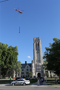 A Helicopter lifts steel beams that are being used to reinforce the bell tower.